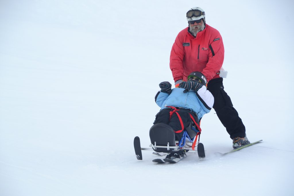 Man pushing someone during the winter ski experience